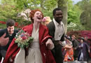 A bride and groom run through a crowd smiling hand in hand