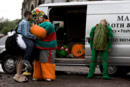 Four men in fancy dress costumes argue in front of a white van