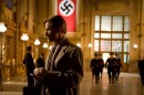 A man stands in a train station with a swastika on a banner behind him and SS officers in the background