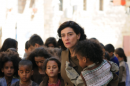 A woman looks concerned whilst leading a group of children.