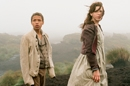 Wide shot of young man and woman in old-fashioned workers clothing stood on a moor